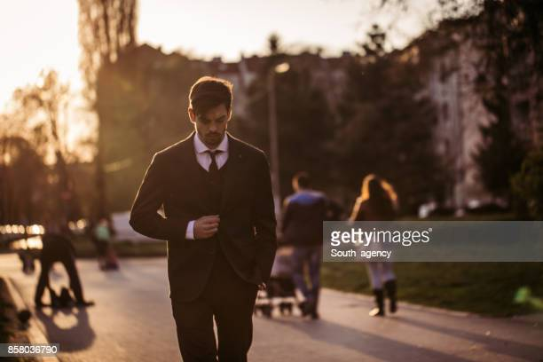 Young businessman walking in park