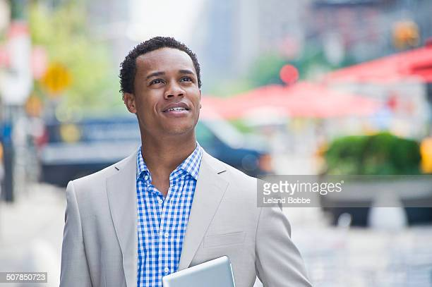 Young businessman walking on city street carrying digital pad