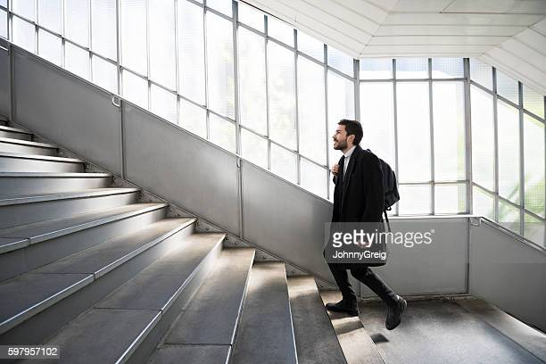 Young businessman walking up stairs at railway station