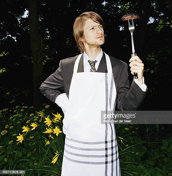 Young businessman wearing apron, looking at sausage on fork