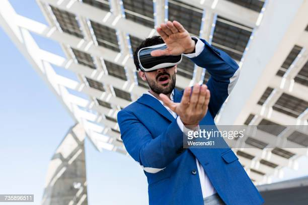 Young businessman wearing VR glasses outdoors