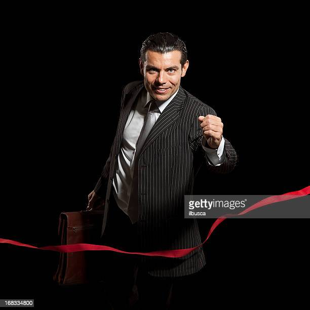Young businessman winning race on finish line