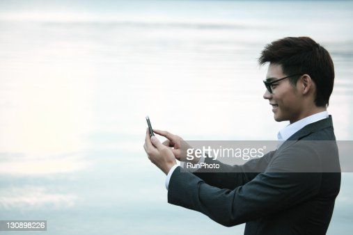 young businessman with a mobile phone in the lake : Stock Photo