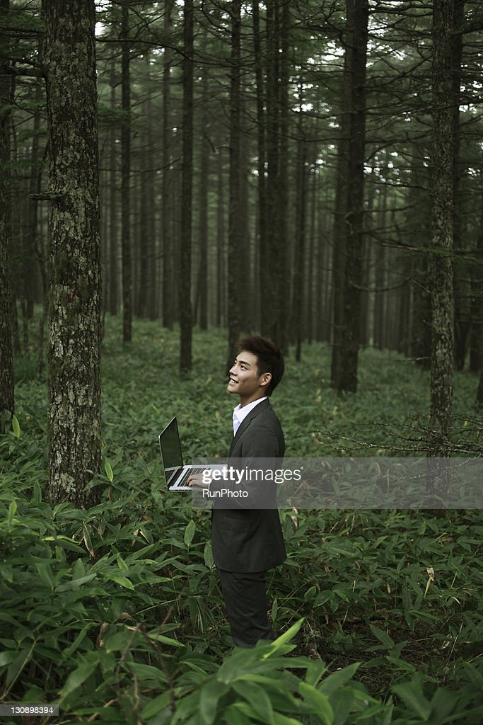 young businessman with a Notebook PC in the forest : Stock Photo