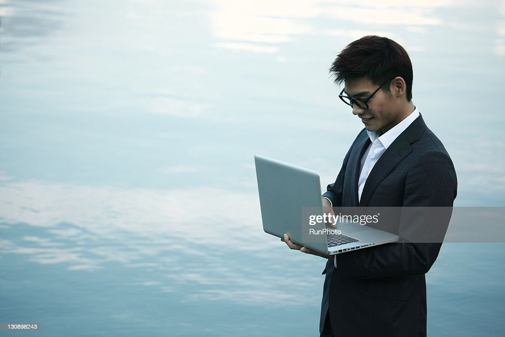 young businessman with a Notebook PC in the lake : Stock Photo