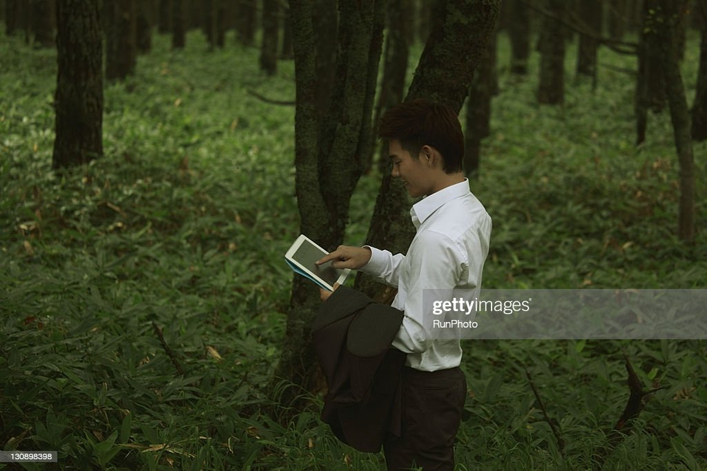 young businessman with a Tablet PC in the forest : Stock Photo