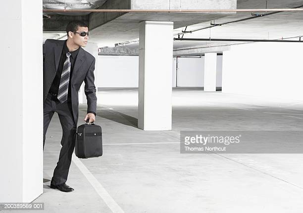 Young businessman with briefcase peeking around wall in parking garage