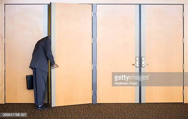 Young businessman with briefcase peeking head around door, rear view
