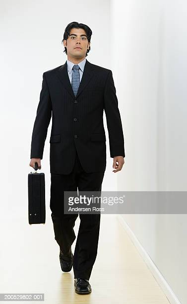 Young businessman with briefcase walking down corridor, portrait