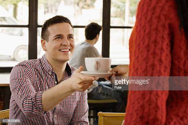 Young businessman with coffee cup sitting in cafe