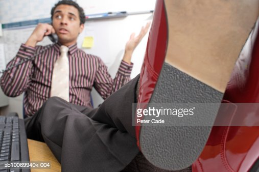 Young businessman with feet resting on desk, using landline phone : Stock Photo