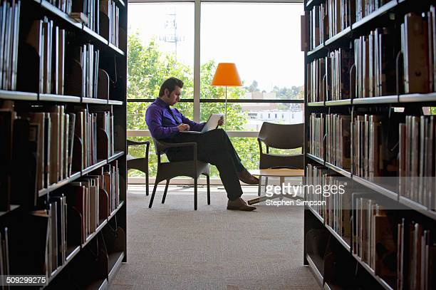 young businessman with laptop in a library