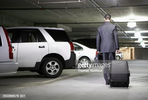 Young businessman with luggage in parking garage, rear view : Stock Photo