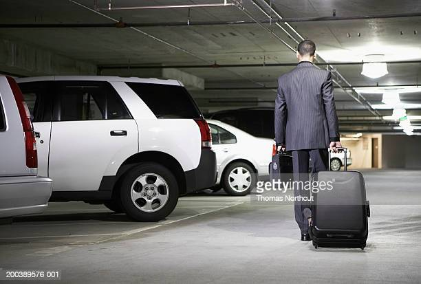 Young businessman with luggage in parking garage, rear view