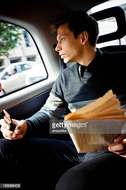 Young Businessman with newspaper in London Cab