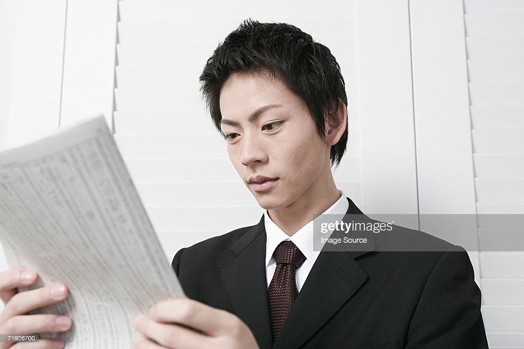 Young businessman with newspaper : Stock Photo