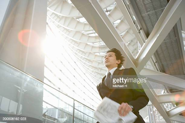 Young businessman with newspaper running down corridor