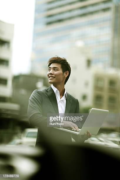 young businessman with PC outside