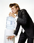 Young businessman with quiffed hair at water cooler
