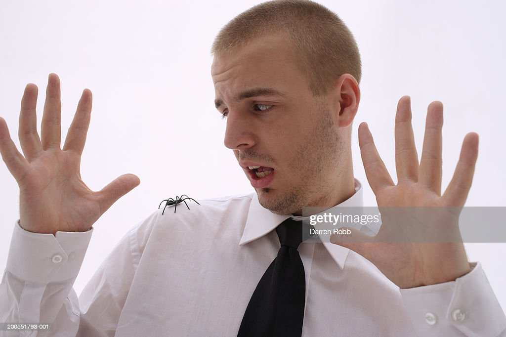 Young businessman with spider on shoulder, close-up