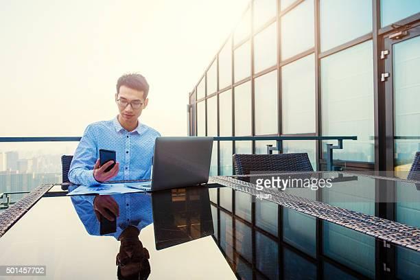 Giovane uomo d'affari, lavorando su un computer portatile e telefono