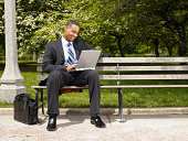 Young businessman working on laptop in park