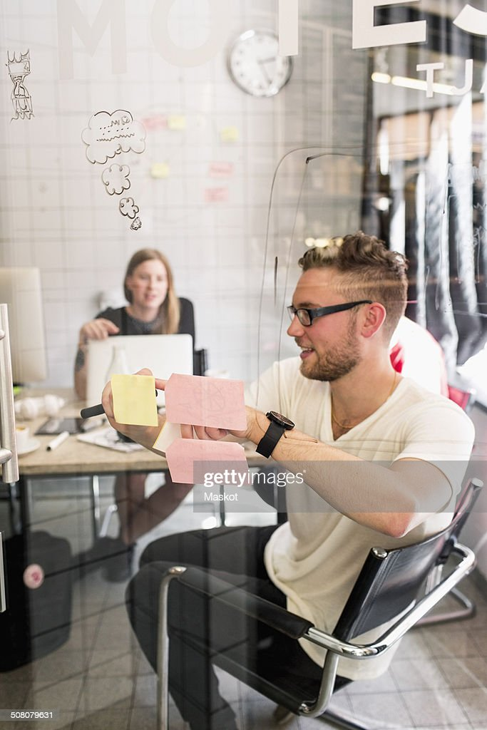 Young businessman writing ideas on adhesive notes with female colleague in background at new office