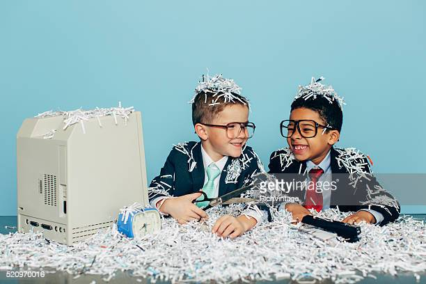 Young Businessmen Covered in Paper at Office Desk Smiling