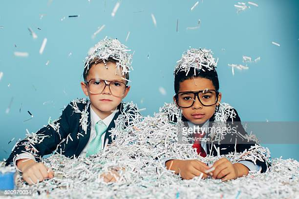 Young Businessmen Covered in Shredded Paper at Office Desk