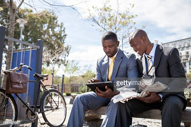 Young businessmen having lunch outside and using tablet
