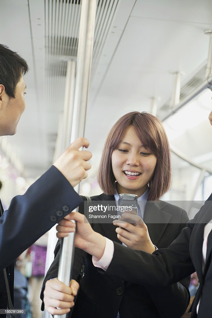 Young Businessmen Looking at Cell Phone in Subway : Stock Photo