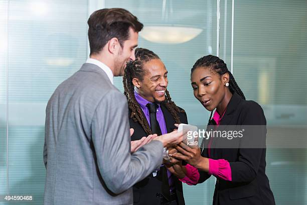 Young businesspeople looking at mobile phone and talking
