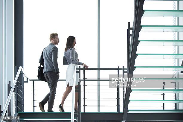 Young businesspeople walking on staircase in hallway.