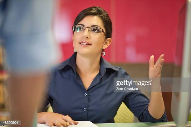 Young businesswoman advising colleague in office