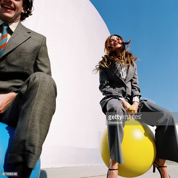 Young businesswoman and a young businessman sitting on space hoppers