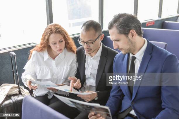 Young businesswoman and businessmen looking at paperwork on passenger ferry