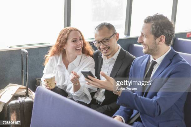 Young businesswoman and businessmen looking at smartphone on passenger ferry