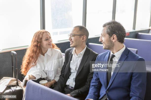 Young businesswoman and businessmen talking on passenger ferry