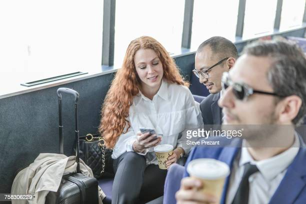 Young businesswoman and man looking at smartphone on passenger ferry