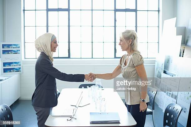 Young businesswoman and mature businesswoman shaking hands in office