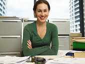 Young businesswoman at desk, smiling, portrait