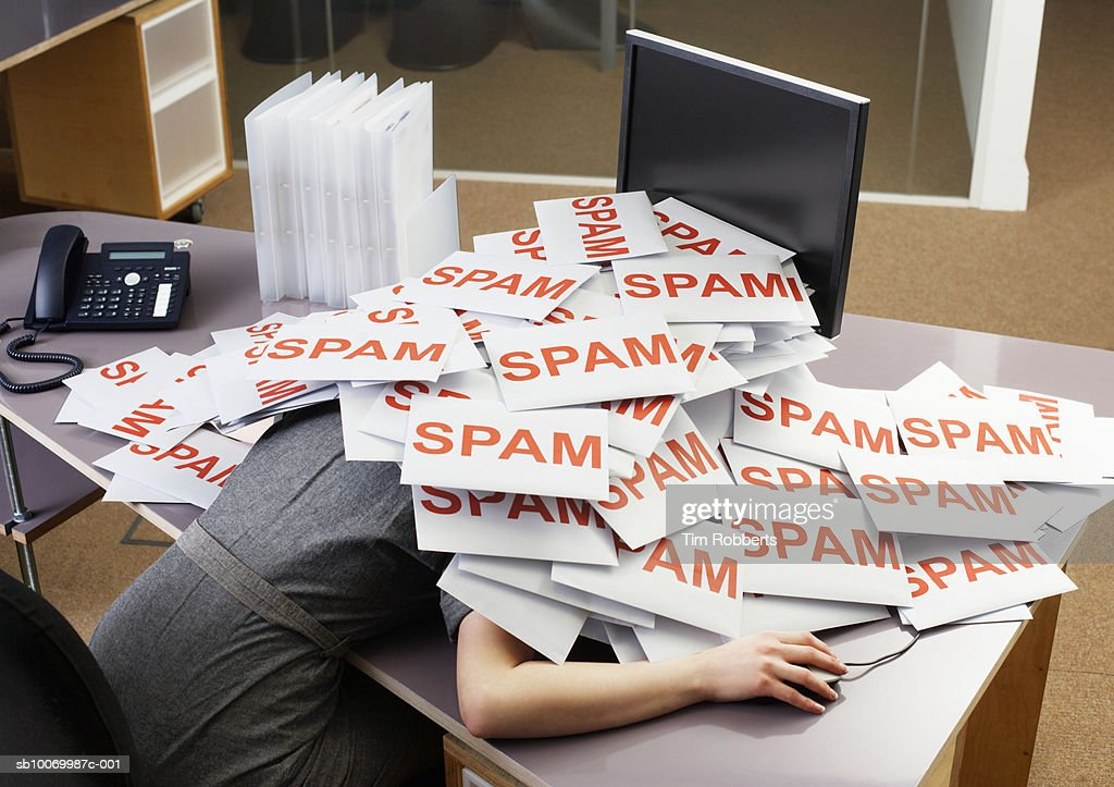 Young businesswoman at office desk with pile of spam envelopes : Foto stock