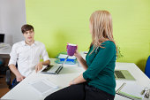 Young businesswoman conversing with male coworker in office break
