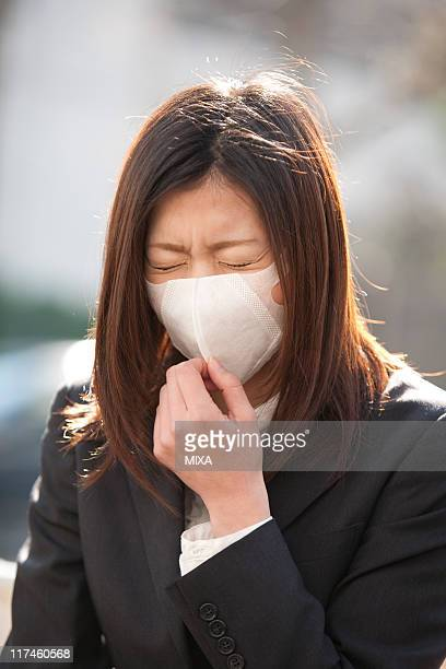 Young businesswoman coughing