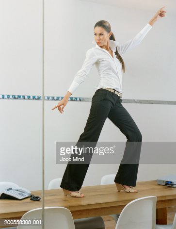 Young businesswoman dancing on desk in office : Stock Photo