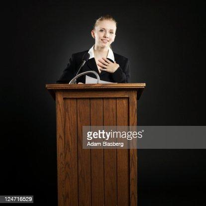 Young businesswoman giving speech at podium : Bildbanksbilder