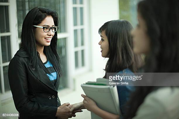 Young businesswoman greeting girls with handshake at office.