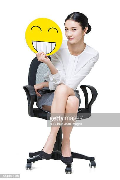 Young businesswoman holding a happy emoticon face