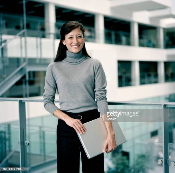 Young businesswoman holding laptop, smiling, portrait