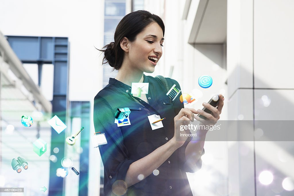 Young businesswoman holding smartphone with apps and icons coming out of it : Stock Photo